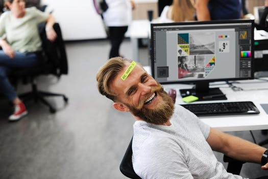 Man at his desk laughing at marketing company in Glasgow